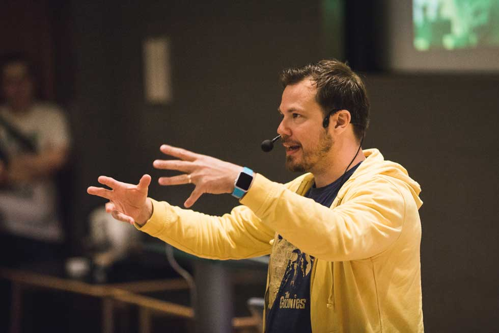 Lauri Järvilehto speaking, man in yellow hoodie